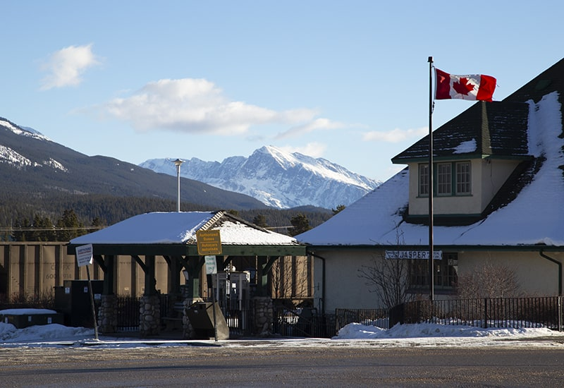 The Jasper Alberta Train Station with a blowing Canada flag