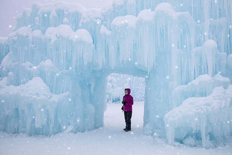 A person stands under the Edmonton Ice Castles
