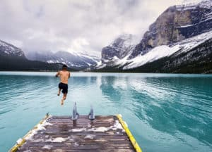 A person takes a plunge into an icy cold mountain lake