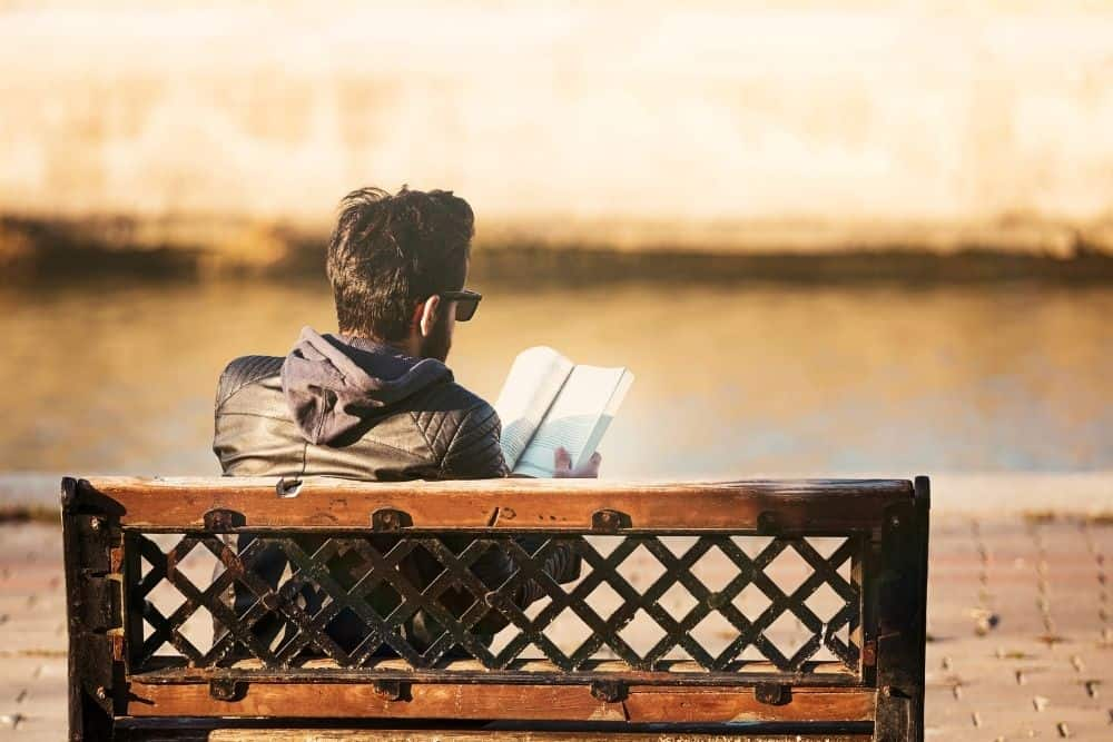A guy reading a book on a bench