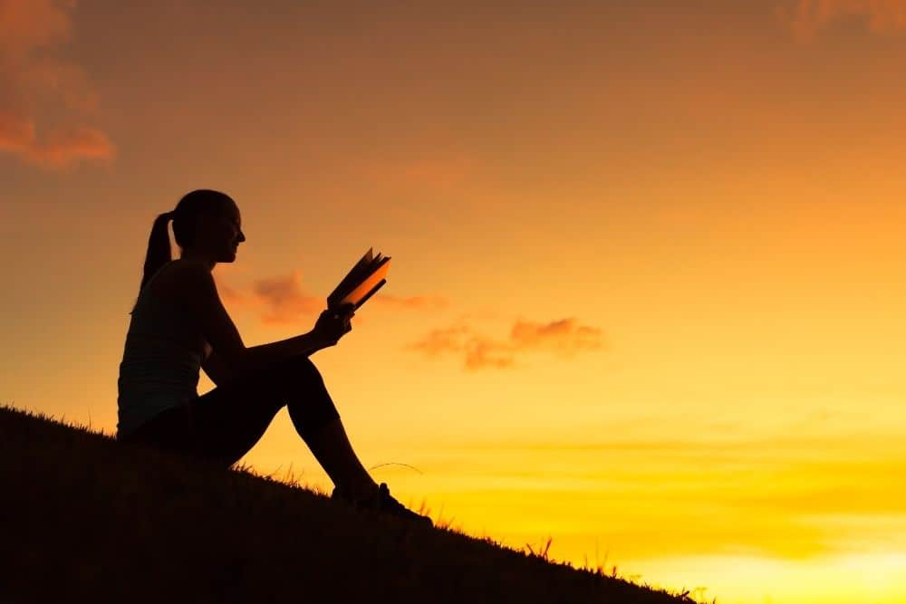 A girl reads on a hill at sunset