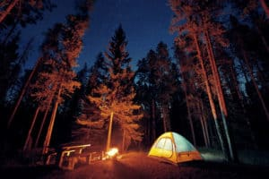Camping at night in a tent by the light of a fire