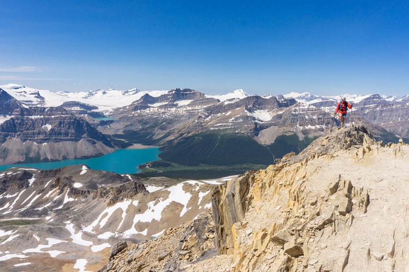 A hiker reaches the summit of Cirque Peak