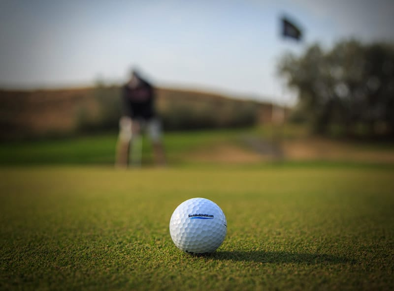 Golf ball and golfer on golf course