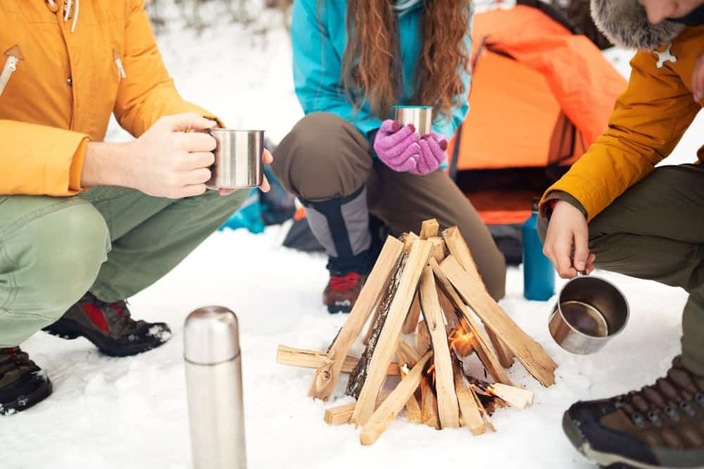 Winter camping starting a campfire