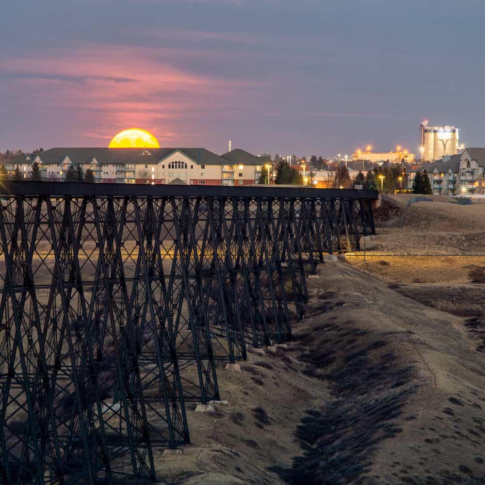 A moon rises over the Lethbridge train bridge