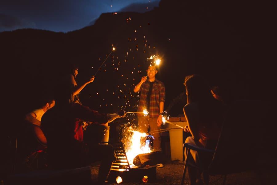 Friends around a fire camping in Banff