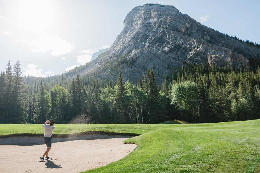 Golfer hits out of the sand bunker at the Fairmont Banff Springs Golf Course