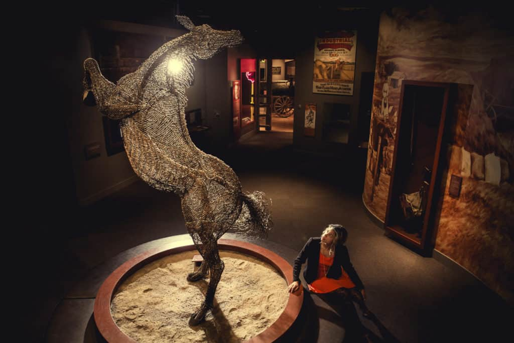 A woman looks at a horse statue in the Glenbow Museum Calgary